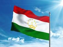 Bandiera del Tagikistan che ondeggia nel cielo blu Fotografia Stock Libera da Diritti
