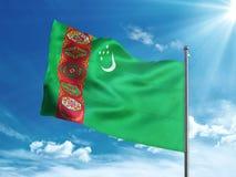Bandiera del Turkmenistan che ondeggia nel cielo blu Fotografie Stock Libere da Diritti