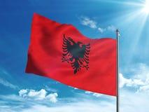 Bandiera dell'Albania che ondeggia nel cielo blu Immagine Stock
