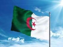 Bandiera dell'Algeria che ondeggia nel cielo blu Immagine Stock