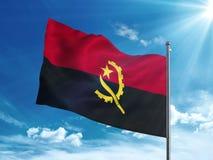 Bandiera dell'Angola che ondeggia nel cielo blu Fotografia Stock