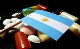 Bandiera dell'Argentina con il lotto delle pillole mediche isolate sul nero Immagini Stock Libere da Diritti