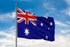 Bandiera dell'Australia che ondeggia nel vento contro il cielo blu nuvoloso bianco Bandierina australiana immagine stock libera da diritti