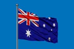 Bandiera dell'Australia che ondeggia nel vento contro il cielo blu profondo Bandierina australiana illustrazione di stock