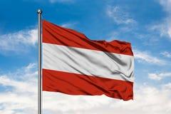 Bandiera dell'Austria che ondeggia nel vento contro il cielo blu nuvoloso bianco bandierina austriaca immagini stock