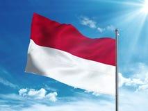 Bandiera dell'Indonesia che ondeggia nel cielo blu Fotografia Stock