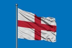 Bandiera dell'Inghilterra che ondeggia nel vento contro il cielo blu profondo Bandierina inglese fotografia stock libera da diritti