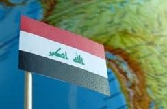 Bandiera dell'Irak con una mappa del globo come fondo Immagine Stock