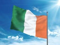 Bandiera dell'Irlanda che ondeggia nel cielo blu Fotografie Stock