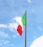 Bandiera dell'Italia contro il cielo nuvoloso blu immagini stock libere da diritti
