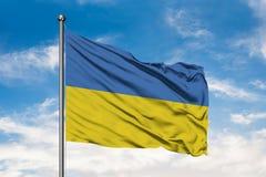 Bandiera dell'Ucraina che ondeggia nel vento contro il cielo blu nuvoloso bianco Bandiera ucraina immagine stock libera da diritti
