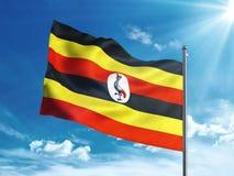 Bandiera dell'Uganda che ondeggia nel cielo blu Immagini Stock Libere da Diritti