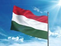 Bandiera dell'Ungheria che ondeggia nel cielo blu Fotografia Stock Libera da Diritti