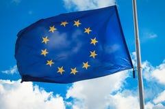 Bandiera dell'Unione Europea contro un cielo nuvoloso blu fotografie stock libere da diritti