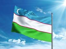 Bandiera dell'Uzbekistan che ondeggia nel cielo blu Fotografie Stock