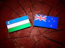 Bandiera dell'Uzbekistan con la bandiera della Nuova Zelanda su un ceppo di albero isolato Fotografia Stock
