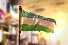 Bandiera dell'Uzbekistan contro fondo vago città ad alba Backl Fotografie Stock