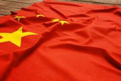 Bandiera della Cina su un fondo di legno dello scrittorio Vista superiore della bandiera cinese di seta fotografia stock