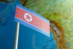 Bandiera della Corea del Nord con una mappa del globo come fondo Fotografia Stock