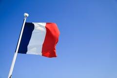 Bandiera della Francia che ondeggia con il chiaro cielo blu immagini stock libere da diritti