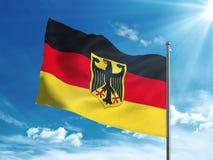 Bandiera della Germania con la stemma che ondeggia nel cielo blu Immagine Stock