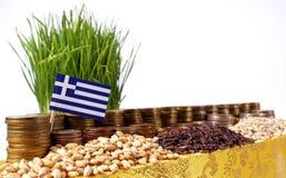 Bandiera della Grecia che ondeggia con la pila di monete dei soldi ed i mucchi di grano Immagine Stock Libera da Diritti