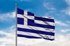 Bandiera della Grecia che ondeggia nel vento contro il cielo blu nuvoloso bianco Bandierina greca fotografia stock