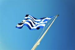 Bandiera della Grecia che ondeggia su un cielo blu immagini stock