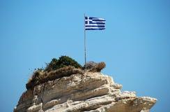 Bandiera della Grecia sulla scogliera al mare Fotografia Stock Libera da Diritti