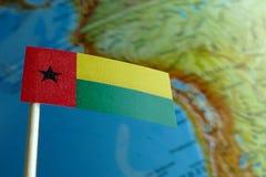 Bandiera della Guinea-Bissau con una mappa del globo come fondo Fotografie Stock
