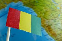 Bandiera della Guinea con una mappa del globo come fondo Immagine Stock Libera da Diritti