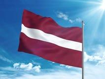 Bandiera della Lettonia che ondeggia nel cielo blu Fotografia Stock Libera da Diritti