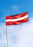 Bandiera della Lettonia sopra cielo blu Fotografia Stock