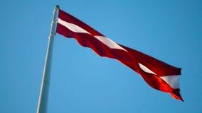 Bandiera della Lettonia sull'alta asta della bandiera enorme che soffia nel vento video d archivio