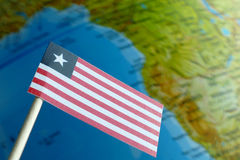 Bandiera della Liberia con una mappa del globo come fondo Immagine Stock