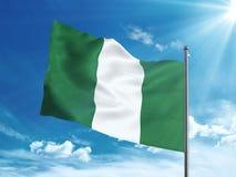 Bandiera della Nigeria che ondeggia nel cielo blu Fotografia Stock Libera da Diritti