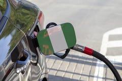 Bandiera della Nigeria sulla falda del riempitore del combustibile del ` s dell'automobile immagini stock libere da diritti