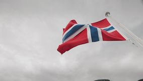 Bandiera della Norvegia che fluttua sopra un cielo tempestoso archivi video