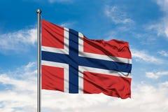 Bandiera della Norvegia che ondeggia nel vento contro il cielo blu nuvoloso bianco Bandierina norvegese fotografia stock libera da diritti