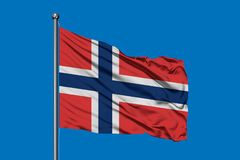 Bandiera della Norvegia che ondeggia nel vento contro il cielo blu profondo Bandierina norvegese fotografia stock