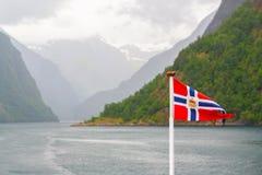 Bandiera della Norvegia che ondeggia sul fiordo della natura della Norvegia fotografia stock libera da diritti