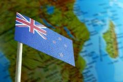 Bandiera della Nuova Zelanda con una mappa del globo come fondo Fotografie Stock