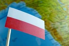 Bandiera della Polonia con una mappa del globo come fondo Immagine Stock