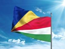 Bandiera della Repubblica delle Seychelles che ondeggia nel cielo blu Fotografia Stock Libera da Diritti