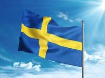 Bandiera della Svezia che ondeggia nel cielo blu Immagine Stock
