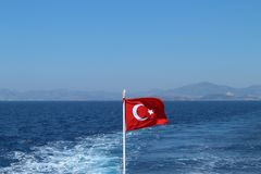 Bandiera della Turchia sui precedenti del mare e delle montagne Fotografia Stock