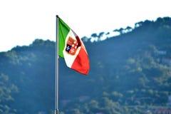 Bandiera delle repubbliche marittime che ondeggiano sul mare con la collina b immagini stock libere da diritti