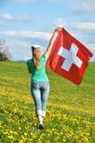 Bandiera dello svizzero della tenuta della ragazza Immagini Stock