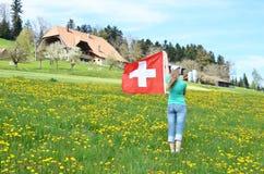 Bandiera dello svizzero della tenuta della ragazza Immagine Stock Libera da Diritti