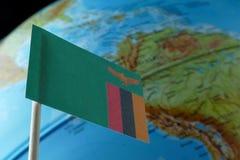Bandiera dello Zambia con una mappa del globo come fondo Fotografia Stock Libera da Diritti
